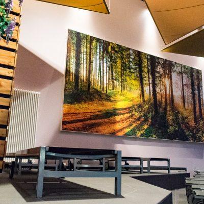 Die Wandgestaltung im warmen grau kombiniert mit dem großen Wandbild schafft eine gemütliche Atmosphäre