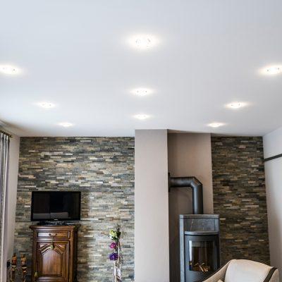 Wohnzimmer nach der Renovierung mit moderner Wandgestaltung und makelloser Spanndecke
